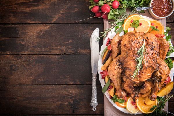 Delicious roasted whole chicken or turkey on plate with cutlery and sauce
